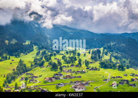 Beautiful view of idyllic mountain scenery in the Alps with old chalets in fresh green meadows, Grindelwald, Bernese - Stock Photo