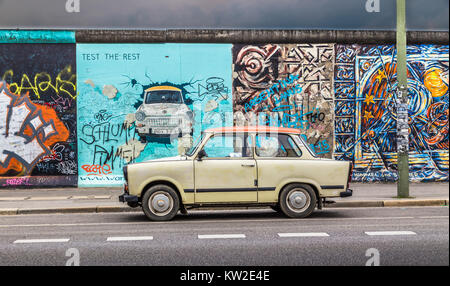 Famous Berliner Mauer (Berlin Wall) at East Side Gallery with an old Trabant, the most common vehicle used in East - Stock Photo