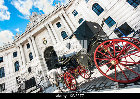 Wide-angle view of famous Hofburg Palace with traditional horse-drawn Fiaker carriages on a sunny day in Vienna, - Stock Photo