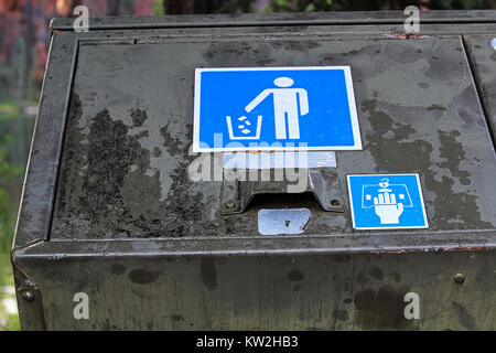 Closeup of a bear proof garbage container latch and sign. - Stock Photo