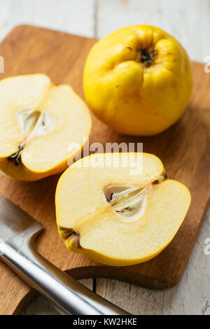 Fresh quince fruit on a cutting board - Stock Photo