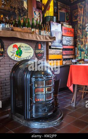 Old coal stove in tavern Kroegske, Belgian café-restaurant in the village Emelgem, Izegem, West Flanders, Belgium - Stock Photo