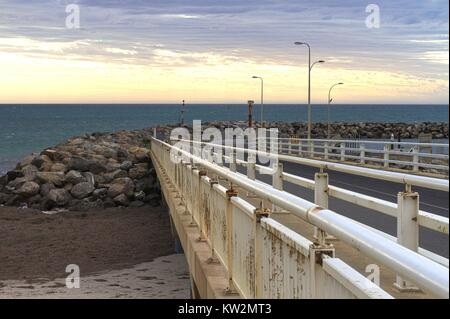 Concrete pier leading out to a rocky breakwater, view of the ocean and sunset. - Stock Photo