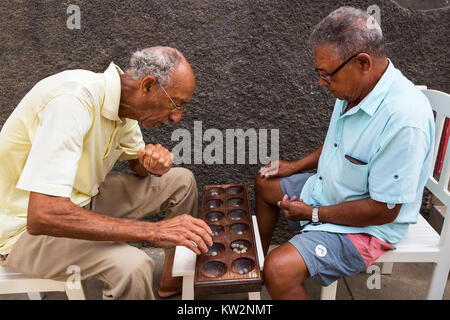 Local men playing the traditional African board game of ouril, also known as mancala, oware, uril, ouri or ori, - Stock Photo