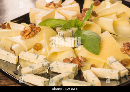 Close up with different types of cheese, on a black plate - Stock Photo