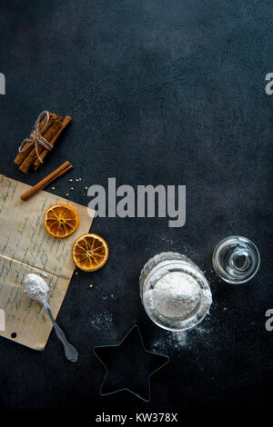 Food preparation. Old recipe, teaspoon, cookie cutter, mason jar with flour and ingredients (cinnamon sticks, dried - Stock Photo