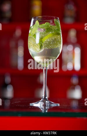 Glass of Hugo cocktail on a background with a blurred bar - Stock Photo