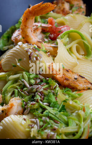 Close up of shrimps and pasta with vegetables on a black plate - Stock Photo