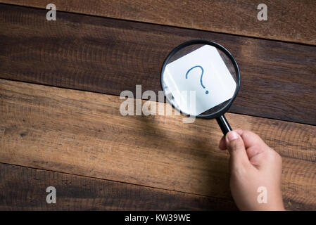 hand holding magnifying glass focusing on question mark. mystery and search concept - Stock Photo