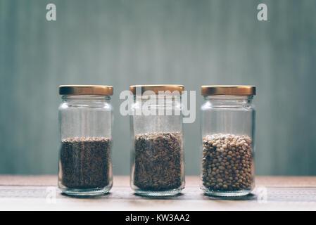 sweet cumin, white cumin and coriander seed in a glass jar on a wooden table - Stock Photo