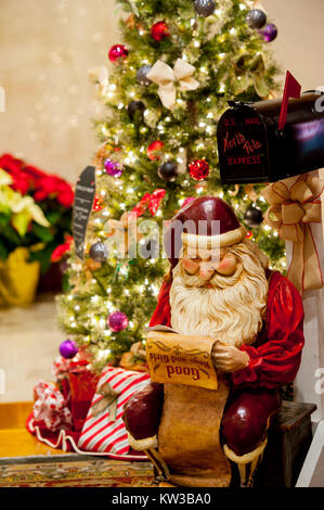 Holidays Christmas a Santa Claus figure is reading a list of boys and girls naughty or nice by a decorated tree - Stock Photo