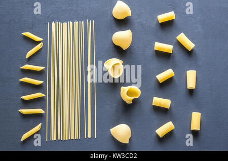 Various types of pasta on the dark background - Stock Photo
