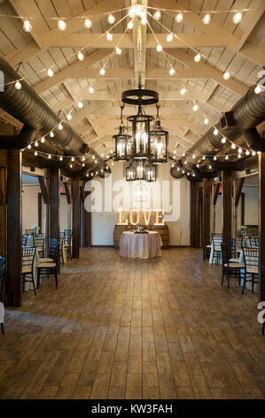 The head table (for bride and groom) in a reception hall - includes sign that says 'Love', spelled out with light - Stock Photo