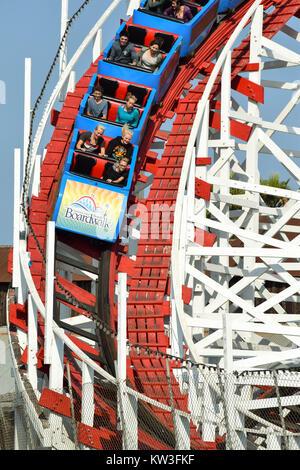 People having fun riding on the Big Dipper-old wooden Roller-coaster, at Santa Cruz Beach Boardwalk, in California - Stock Photo