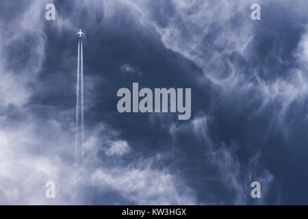 Far away jet plane travelling straight up with vapor trails against blue cloudy sky. - Stock Photo