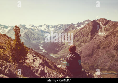 guy sitting hill. The guy sits on a hill and looks out into the distance. longest river in the gorge. Lonely man - Stock Photo