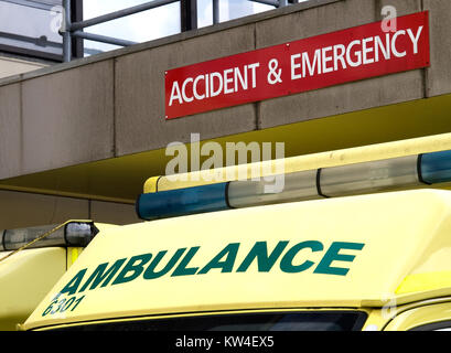 Roof of an ambulance cab showing light bar and ambulance signage parked outside an Accident and Emergency department - Stock Photo