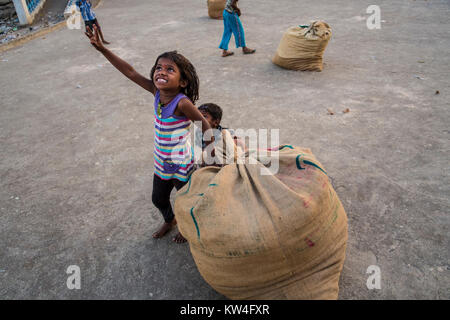 A little girl gets all excited looking at a airplane flyimng overhead as she manages a large gunny sack of dried - Stock Photo