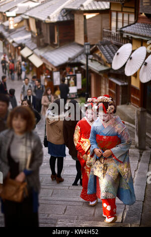 Two Maiko, Geisha apprentices, in colorful kimono walking on an old street Yasaka dori among people in Kyoto, near - Stock Photo