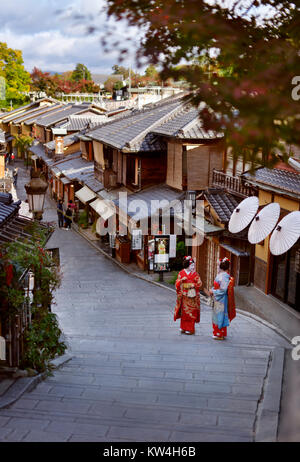 Two Maiko, Geisha apprentices in colorful kimono standing on an old street Yasaka dori in Kyoto, near Kiyomizu-dera - Stock Photo
