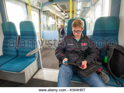 Young man playing video games on a Nintendo Switch while traveling in a Southern Railway coach car, England, United - Stock Photo
