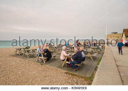 People sitting on picnic benches with Martello Tower number 74 in background, Seaford Beach, Lewes District, East - Stock Photo