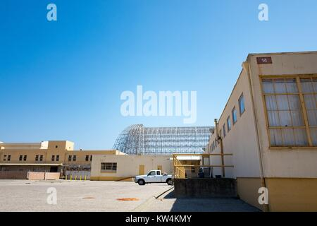 The exposed metal frame of Hanger One is visible behind building 14 within the secure area of the NASA Ames Research - Stock Photo