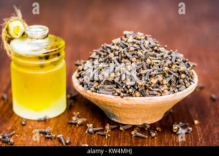 raw cloves,Syzygium aromaticum in a clay bowl with its oil beneficial for skin care and health care. - Stock Photo