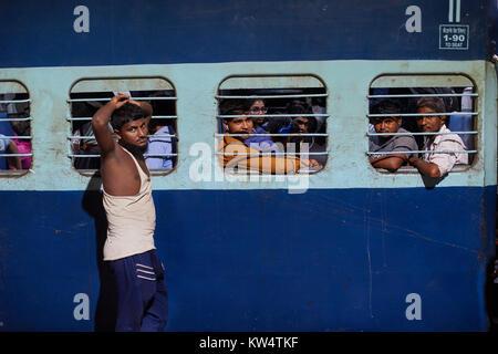 Indian men at train windows, Hazrat Nizamuddin railway station, Delhi, India - Stock Photo