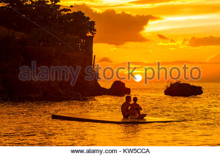 A silhouetted couple watch a romantic sunset from a floating dock in Ocho Rios, Jamaica. - Stock Photo