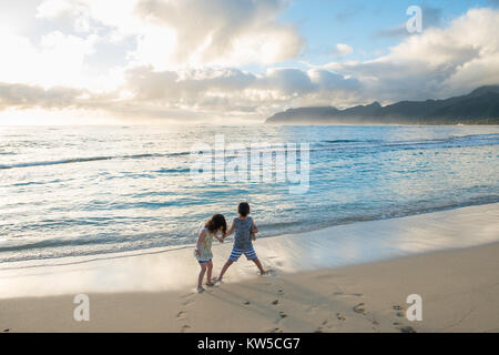 Siblings experiencing the beach and ocean together while on a tropical vacation to Oahu Hawaii with nice warm weather - Stock Photo