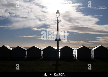 a line of 7 Beach huts and a street lamp silhoutted black by the sun shining directly at the camera through a dramatic - Stock Photo