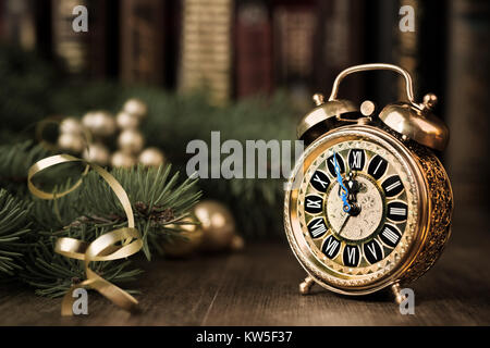 Vintage alarm clock in traditional study room showing five to midnight. Happy New Year!