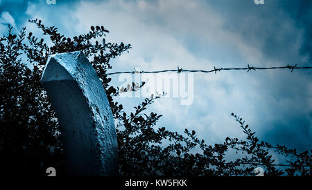 Beyond the barbed wire. Melancholy twilight. Sad view of blue sky in moonlight through the spiked fence. Dramatic - Stock Photo