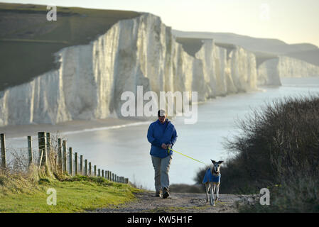 Person walking a dog on the South Downs, East Sussex, with the famous Seven Sisters chalk cliffs behind. - Stock Photo