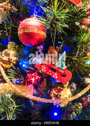 A close up of a Christmas tree decorated with baubles and colourful fairly light. This is a festive tradition in - Stock Photo