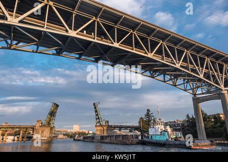 Tugboats taking a barge through to University Bridge and under the I 5 bridge, Seattle, Washington, USA - Stock Photo