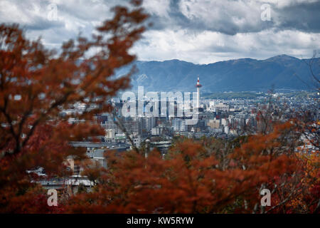 Kyoto tower under dramatic sky in aerial city scenery through red autumn tree leaves. Higashiyama, Kyoto, Japan - Stock Photo
