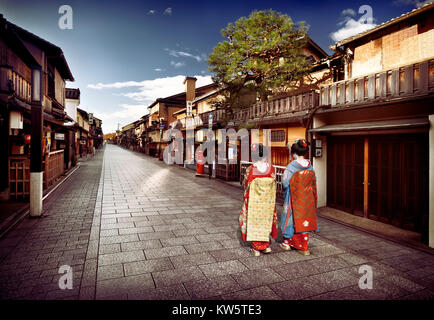 Two Maiko, Geisha apprentices in beautiful colorful kimono with long obi walking along empty Hanamikoji Dori street - Stock Photo