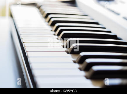 An electronic keyboard is in a bright room placed next to an open window. This is a bright image with the focus - Stock Photo