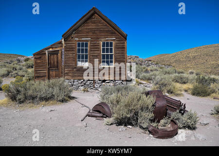 Pieces of an old car in front of an old house,with dry shrubs, rolling hills in the background, and a deep blue - Stock Photo