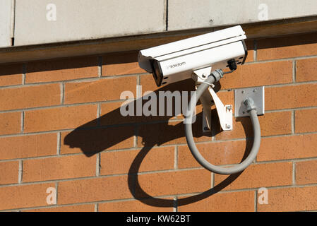 A surveillance camera on a brick wall of a store in Gloversville, NY USA - Stock Photo