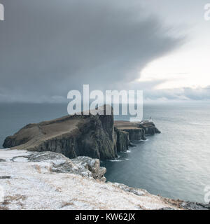 Neist Point Peninsula with White Lighthouse - Isle of Skye Landscape with Stormy Clouds on Sky, Dramatic Cliffs - Stock Photo