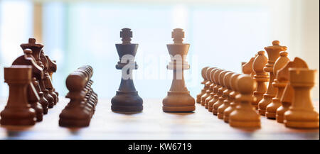 Chessboard blurred with chess pieces on it. Close up view with details, white backdrop. - Stock Photo