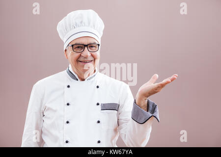 Portrait of restaurant's chef in working uniform greeting guests - Stock Photo