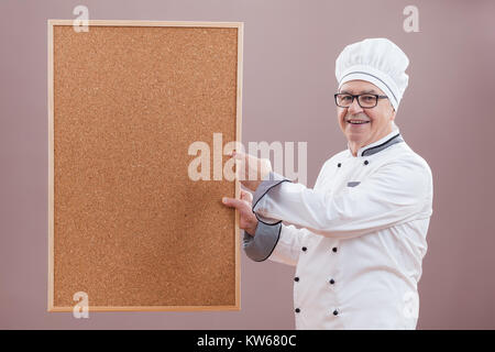 Portrait of restaurant's chef in working uniform showing what is on menu - Stock Photo