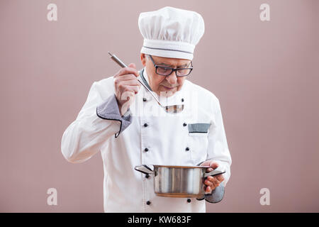 Portrait of restaurant's chef in working uniform tasting the meal - Stock Photo