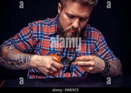 Leather man at work on his new leather product - Stock Photo