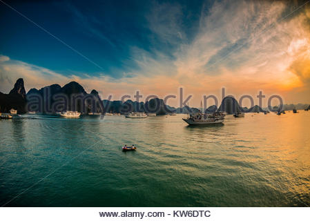 Sunset in Halong Bay, North Vietnam. The bay features 3,000  limestone and dolomite karsts and islets in various - Stock Photo