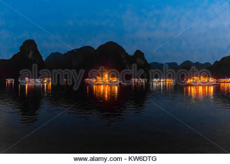Tour ships docked for the night in Halong Bay, North Vietnam. The bay features 3,000  limestone and dolomite karsts - Stock Photo